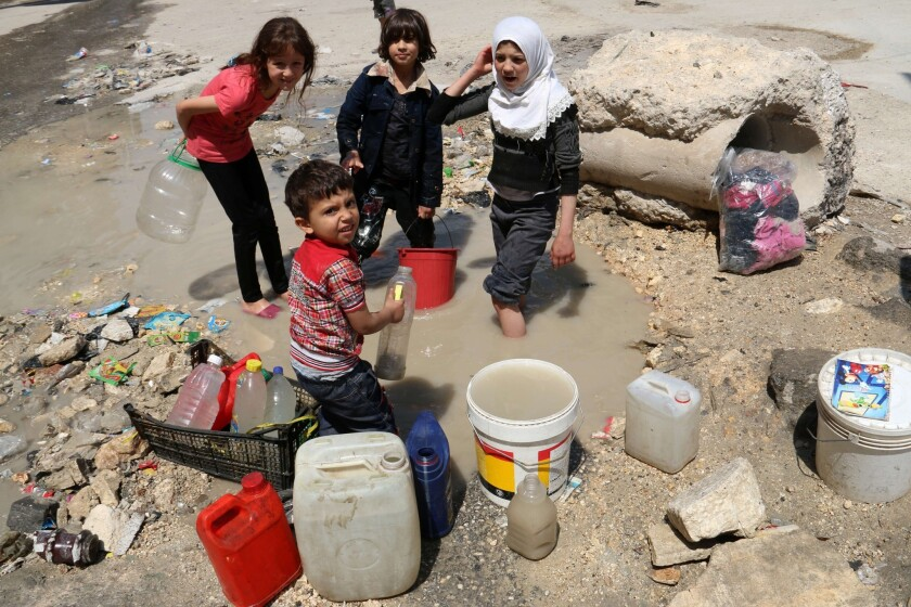 Syrian children collect water from the side of a road in the northern Syria city of Aleppo.