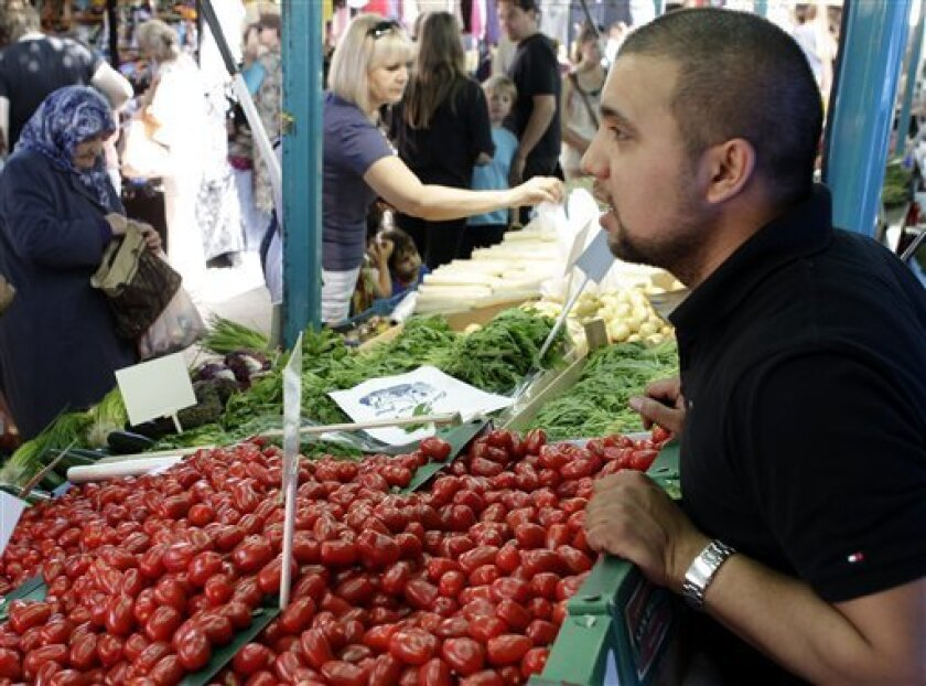 CORRECTS FIRST NAME OF THE DEALER- Dealer Mehmet Tanis stays behind tomatoes at his market stand in Berlin, Germany, Friday, June 3, 2011. Nearly 200 new cases of E. coli infection were reported in Germany in the first two days of June, the national disease control center reported Friday, but officials say there are signs the European bacterial outbreak that has killed 18 people could be slowing. While suspicion has fallen on raw tomatoes, cucumbers and lettuce as the source of the germ, researchers have been unable to pinpoint the food responsible.(AP Photo/Michael Sohn)