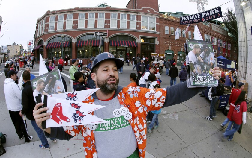 FILE - In this Oct. 19, 2013, file photo, Tim Lampa hawks programs and Boston Red Sox pennants outside Fenway Park before Game 6 of the American League baseball championship series between the Red Sox and the Detroit Tigers in Boston. Ballpark area businesses are struggling during the 2020 season while fans are not in attendance due to the COVID-19 pandemic. (AP Photo/Charlie Riedel, File)