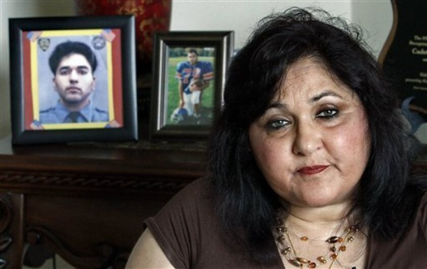In this Tuesday, Aug. 17, 2010 photo, seated next to portraits of her son Mohammad Salman Hamdani, who was 23 when he died attempting to save lives at the World Trade Center on Sept. 11, 2001, Talat Hamdani sits during an interview in New York.  (AP Photo/Bebeto Matthews)