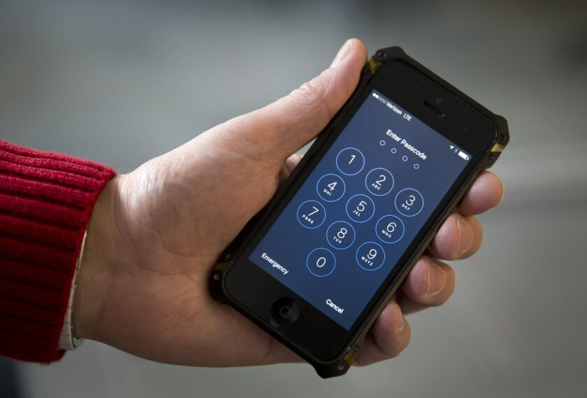 An iPhone is seen in Washington, Wednesday, Feb. 17, 2016. The San Bernardino County-owned iPhone at the center of an unfolding high-profile legal battle between Apple Inc. and the U.S. government lacked a device management feature bought by the county that, if installed, would have allowed investigators easy and immediate access. (AP Photo/Carolyn Kaster)
