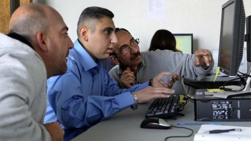 Luay Aziz, center, a refugee from Iraq, volunteers at the International Rescue Committee