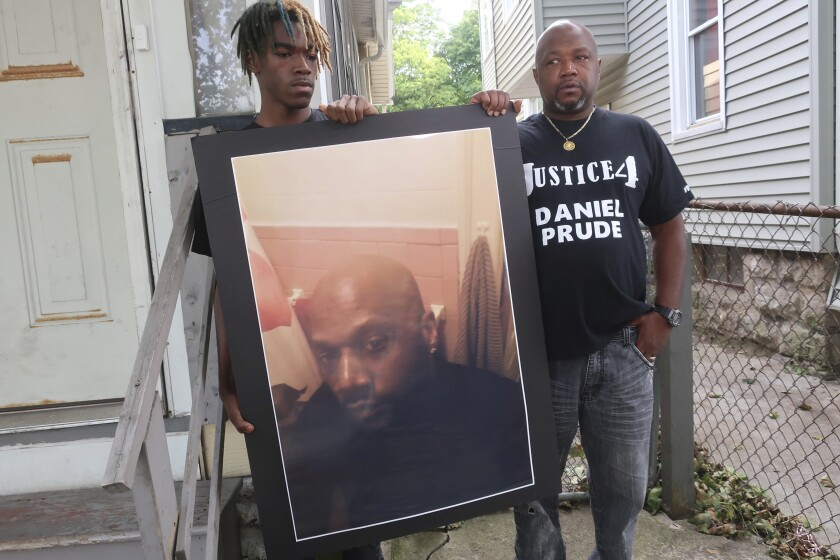 """FILE - Joe Prude, brother of Daniel Prude, right, and his son Armin, stand with a picture of Daniel Prude in Rochester, N.Y., on Thursday, Sept. 3, 2020. One of several police officers seen on video pinning down Prude, a Black man who died after being detained on a street in upstate New York, faces potential departmental discipline, the Rochester Police Department said. Officer Mark Vaughn is the only officer to be served with """"departmental charges"""" Thursday following an internal investigation of the police response to Prude, whose death sparked nightly protests and led to the suspension of seven officers. (AP Photo/Ted Shaffrey, File)"""