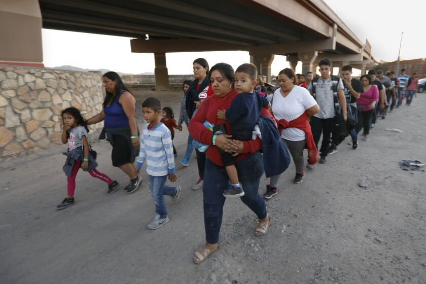 Migrants are led to a holding area after crossing the U.S.-Mexico border