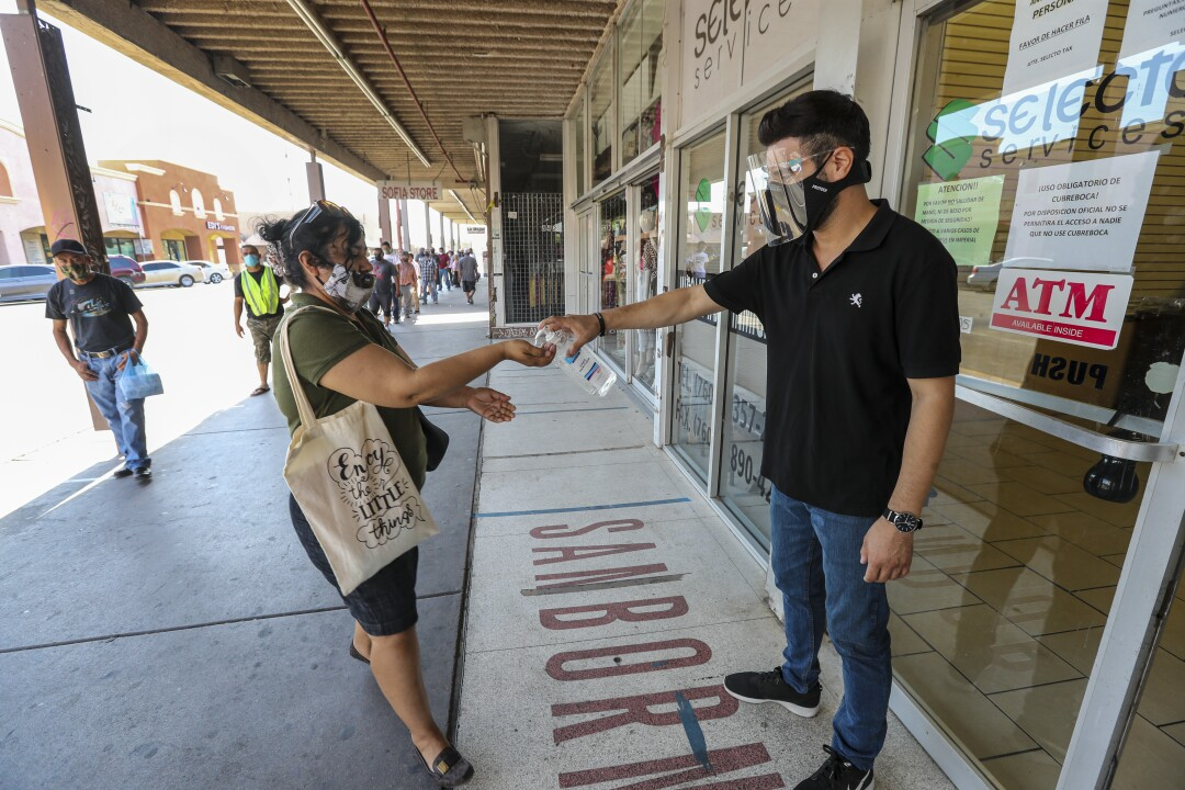 Emmanuel Vazquez squirts hand sanitizer into a woman's hand outside a private service agency in Calexico.