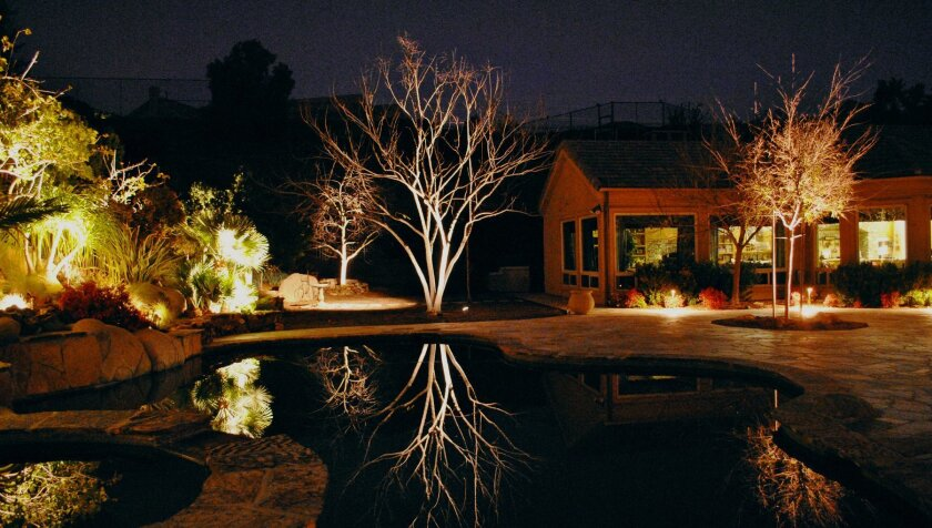 Lit trees are reflected in the swimming pool at a home in Poway.