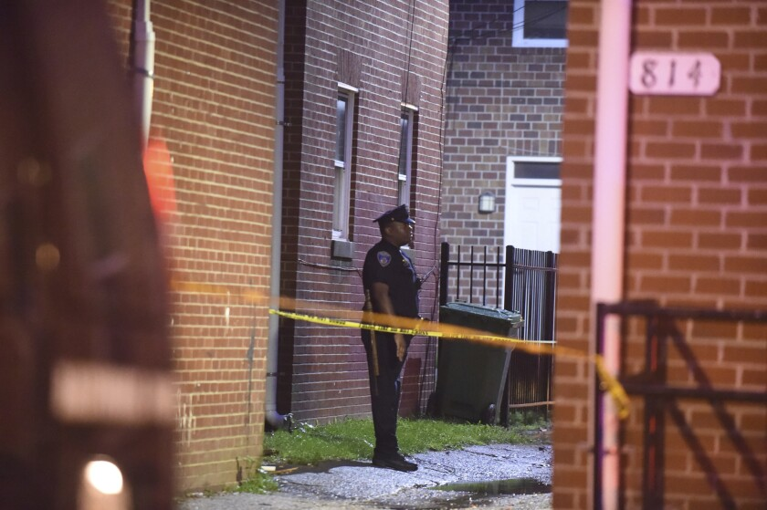 A police officer stands near the scene of a shooting in Baltimore last month.