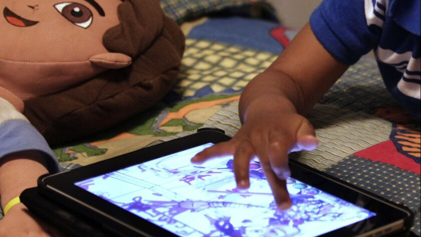 FILE - In this Friday, Oct. 21, 2011, file photo, a child plays with an iPad in his bedroom. Parents