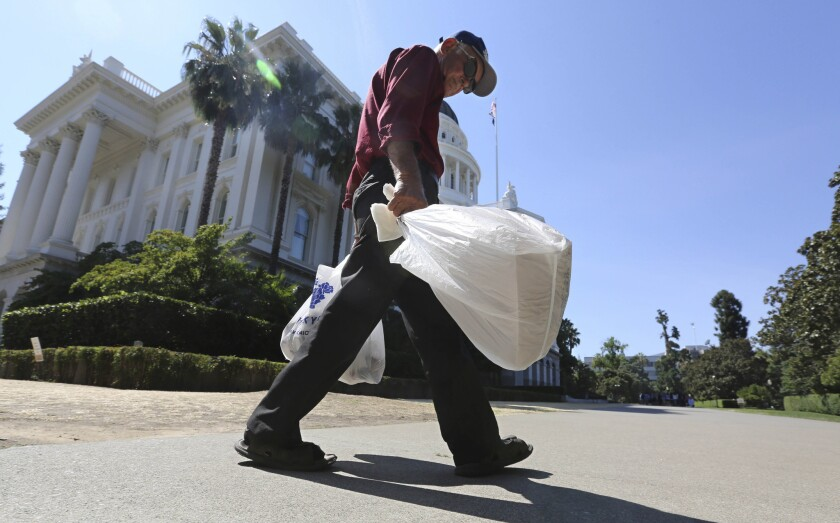 A man carries plastic single-use bags past the state Capitol in Sacramento.