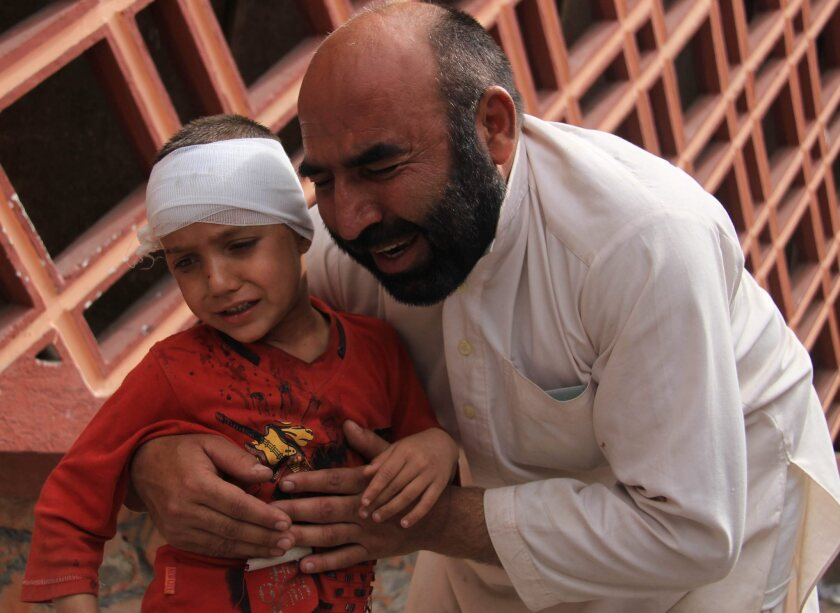A boys is held by his father outside a hospital where he was treated after a suicide bomb attack April 18, 2015, in Jalalabad, Afghanistan.
