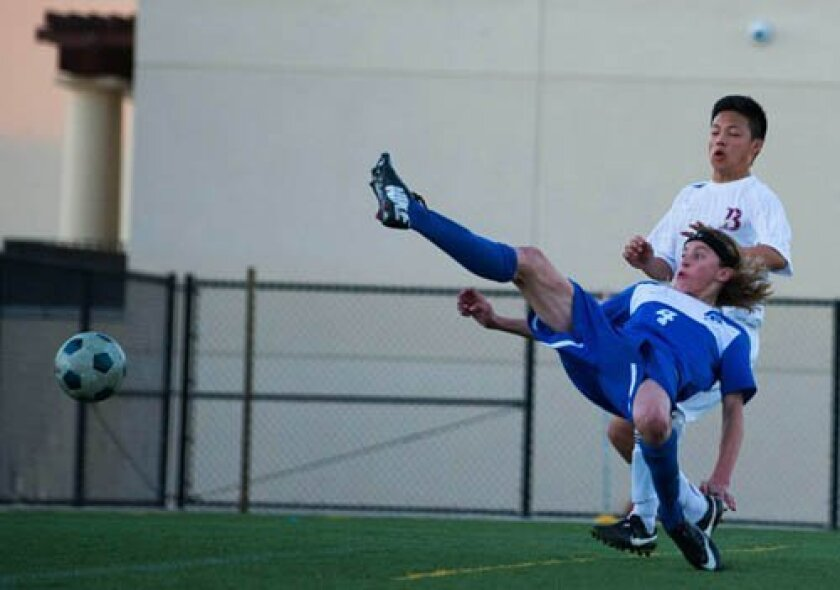 La Jolla Country Day School's Grayson Lyman (4) attempts sprawled kick in front of Bishop's goal in waning minutes with Torrey's down a goal. Defending is Jihadi Cheng of Bishop's. Photo by Ed Piper