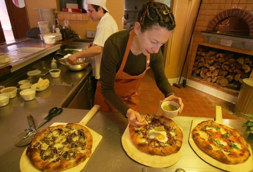 TOPPING IT OFF: Nancy Silverton finishes a pizza.