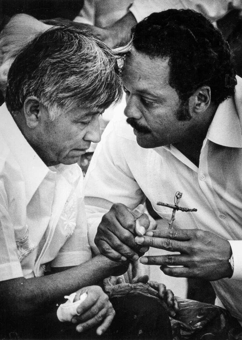 Aug. 21, 1988: Cesar Chavez, left, passes a wooden cross to Jesse Jackson during a Mass to end his 36-day fast protesting use of pesticides on table grapes. This photo was published in the Aug. 22, 1988, LA Times.