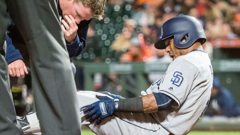 Padres shortstop Erick Aybar (8) is examined by a staff member after an injury against the San Francisco Giants during the ninth inning at AT&T Park.