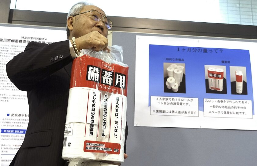 Satoshi Kurosaki, an industry executive who is leading the toilet pear campaign, shows the emergency stock toilet paper at Ministry of Economy, Trade and Industry during an event marking Monday's national disaster prevention day in Tokyo, Monday, Sept. 1, 2014. On national disaster prevention day, Japan's government is urging people to stock up on toilet paper, because more than 40 percent of the nation's supply comes from a high-risk earthquake zone. (AP Photo/Mari Yamaguchi)