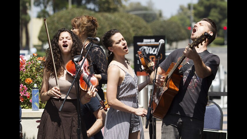 """Cast members Marnina Schon, Cassidy Stirtz and Scott Anthony, from left, from the upcoming musical """"Once"""" showcase their skills as rousing musicians during a noontime gig in front of South Coast Repertory on Wednesday."""