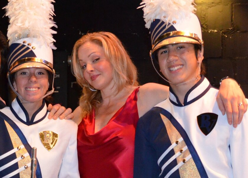 Storm Large (center), one of the two female singers in Pink Martini, poses with Bonita Vista High School Club Blue marching band members Lorena Lopez (left) and Kyle McConkey at San Diego's Balboa Theatre. Pink Martini returns to the Balboa for a Jan. 29 concert. Tickets go on sale this week.