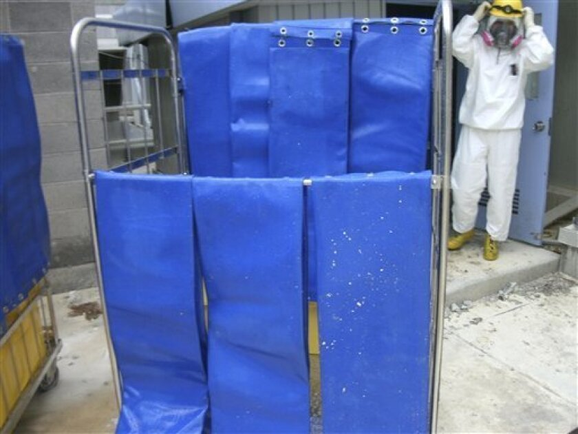 In this photo taken on June 21, 2011 and released on Thursday, June 23, 2011 by Tokyo Electric Power Co. (TEPCO), a worker in a protective suit stands by radiation shield mats which are used to protect workers in the Unit 2 reactor building at the tsunami-damaged Fukushima Dai-ichi nuclear plant in Okuma, Fukushima prefecture, northeastern Japan. (AP Photo/Tokyo Electric Power Co.)