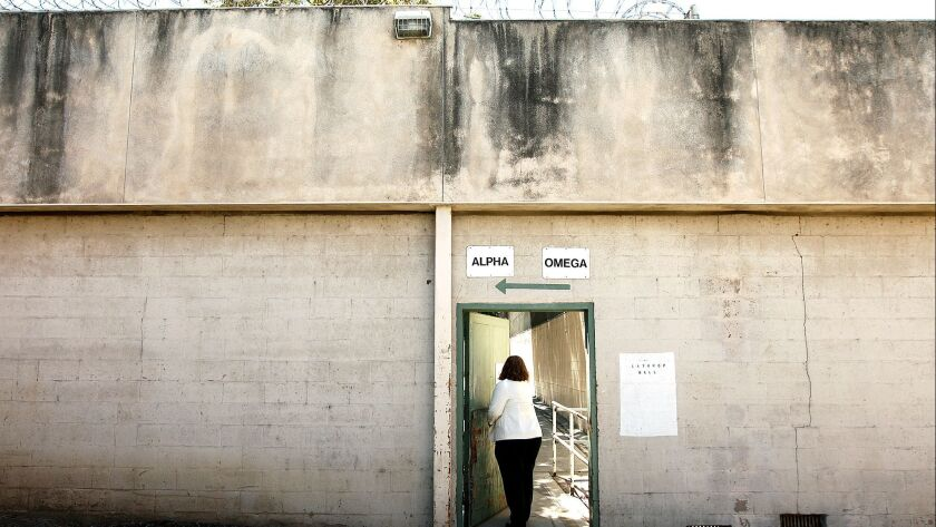LOS ANGELES-CA-JULY 23, 2014: Services Director Melissa Stutenroth passes through an old walkway at