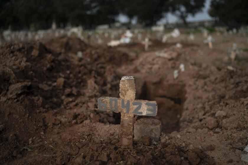 A cross marks the grave of Paulo Jose da Silva, 57, who died of COVID-19 in Rio de Janeiro.