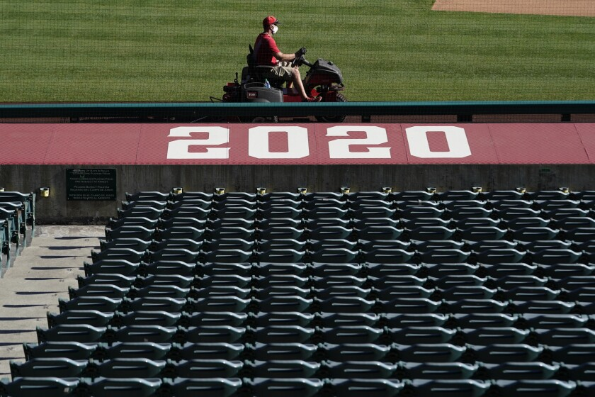 A member of the grounds crew rides a mower past empty stands before Los Angeles Angels baseball practice.