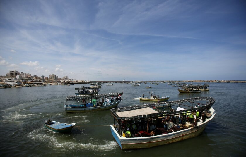 FILE - In this Monday, May 19, 2014 file photo, Palestinian boats head out to sea during a protest organized by Palestinian activists against the Israeli naval blockade, at the fishermen's port in Gaza City. A deal on ending the monthlong Gaza war could hinge on a seaport for the territory on the Mediterranean coast that is blockaded by Israel and Egypt. (AP Photo/Hatem Moussa, File)