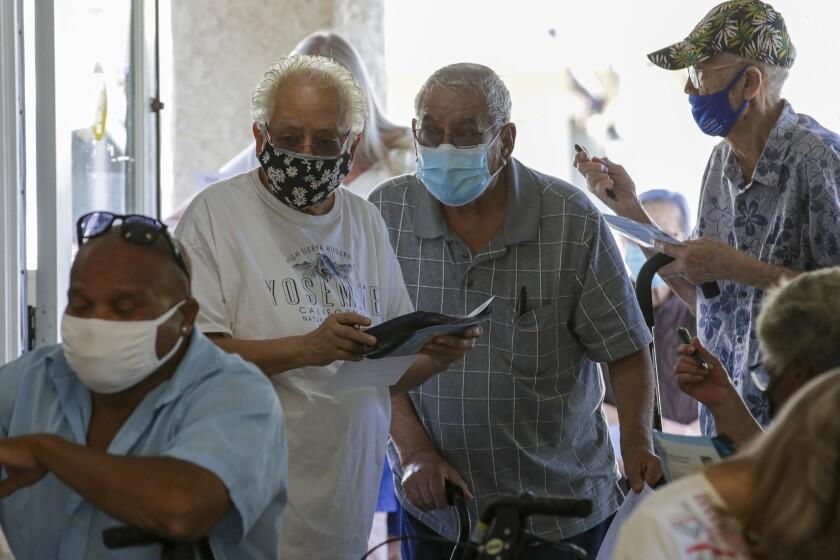 Older men in face masks stand in a line.