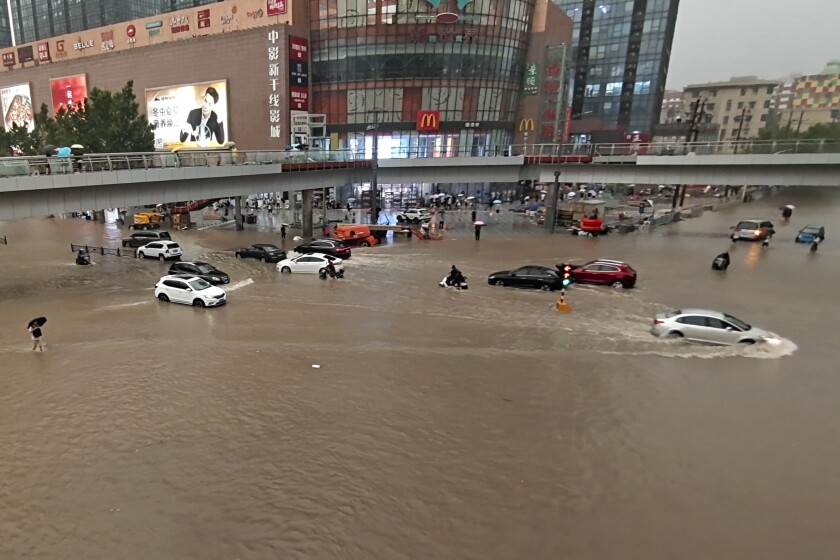 Vehicles are stranded after a heavy downpour in Zhengzhou city in central China's Henan province on July 20.