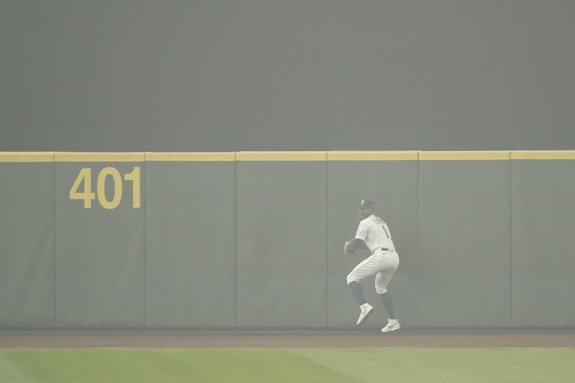 Seattle Mariners center fielder Kyle Lewis prepares to throw the ball back to the infield after making a catch as the air is filled with wildfire smoke during the first baseball game of a doubleheader against the Oakland Athletics, Monday, Sept. 14, 2020, in Seattle. (AP Photo/Ted S. Warren)