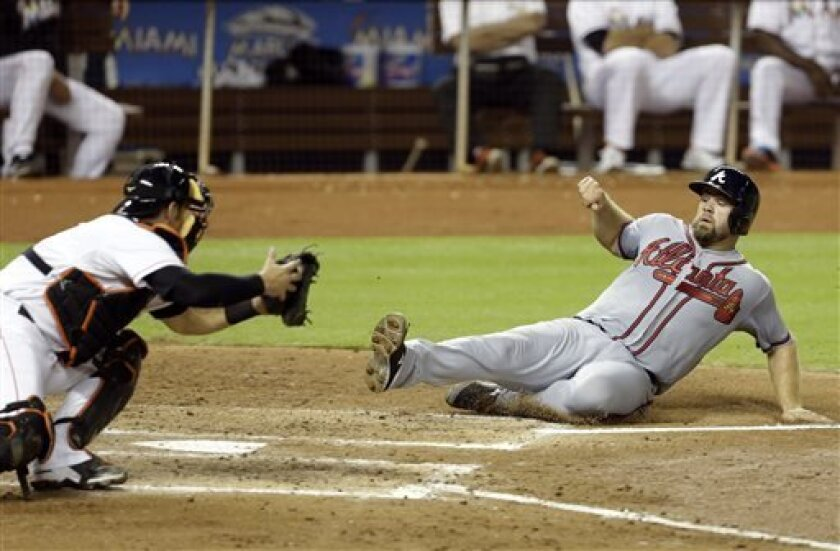Atlanta Braves' Evan Gattis, right, beats the throw to Miami Marlins catcher Jeff Mathis, left, to score on a single by Chris Johnson in the fourth inning during a baseball game, Monday, Sept. 9, 2013 in Miami. (AP Photo/Lynne Sladky)