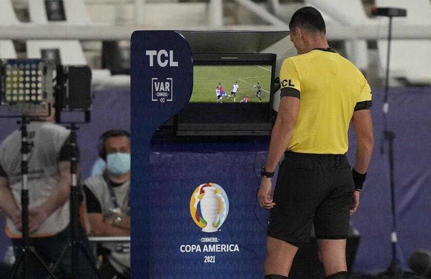 El árbitro Wilmar Roldán revisa el VAR durante el partido entre Argentina y Chile por la Copa América.