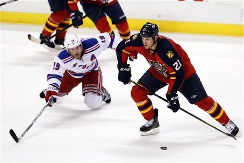 New York Rangers center Brad Richards (19) and Florida Panthers right wing Krys Barch (21) battle for the puck during the third period of an NHL hockey game, Friday, Dec. 30, 2011, in Sunrise, Fla. The Rangers won 4-1. (AP Photo/Wilfredo Lee)