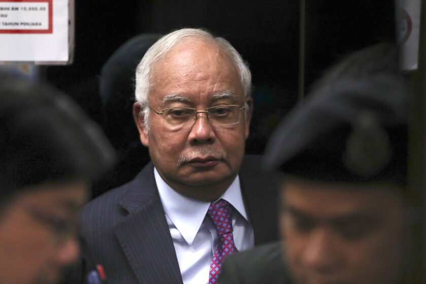 FILE - In this June 18, 2019, file photo, former Malaysian Prime Minister Najib Razak walks into the lift as he arrives at Kuala Lumpur High Court in Kuala Lumpur, Malaysia. Malaysia has ordered 80 people and groups to pay fines totaling about $100 million for allegedly receiving funds from the 1MDB state investment fund. Najib faces 42 charges of corruption, abuse of power and money laundering in five separate criminal cases linked to the multibillion-dollar looting of 1MDB. (AP Photo/Vincent Thian, File)