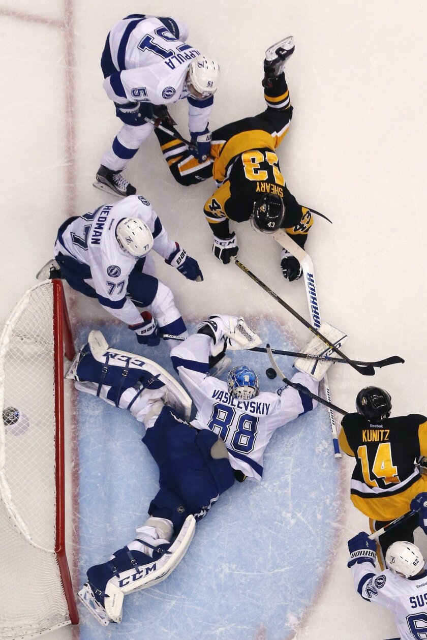 Tampa Bay Lightning goalie Andrei Vasilevskiy (88) sprawls in the goal crease as Pittsburgh Penguins' Chris Kunitz (14) and Nick Bonino (13) try to get their sticks on the loose puck with Lightning's Victor Hedman (77) and Valtteri Filppula (51) defending during the second period of Game 7 of the N