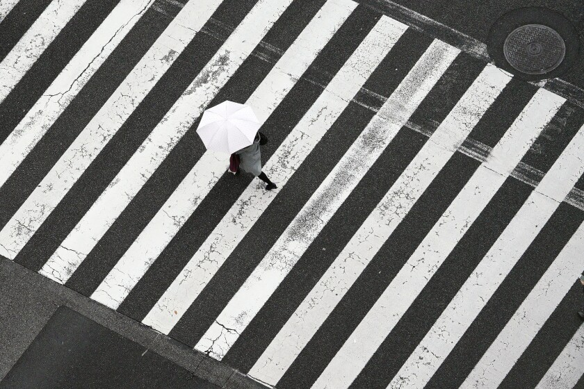 In this Dec. 19, 2019, photo, a woman walks on the pedestrian crossing in the rain in Tokyo. Japan's economy contracted at a dismal 7.1% annual rate during the October-December period, worse than the initial estimate, raising fears the world's third largest economy could be headed to a recession. (AP Photo/Eugene Hoshiko)