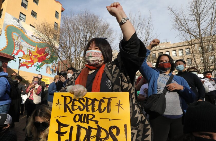 """An Asian American woman holds up a sign that says """"Respect our elders!"""""""
