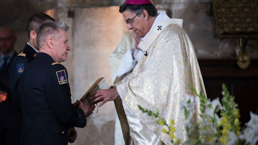Archbishop of Paris Michel Aupetit gives a Bible saved from the flames at the Notre Dame Cathedral to the French general firefighter Jean Claude Gallet during a Mass in tribute at the Saint Eustache Church in Paris on Sunday.