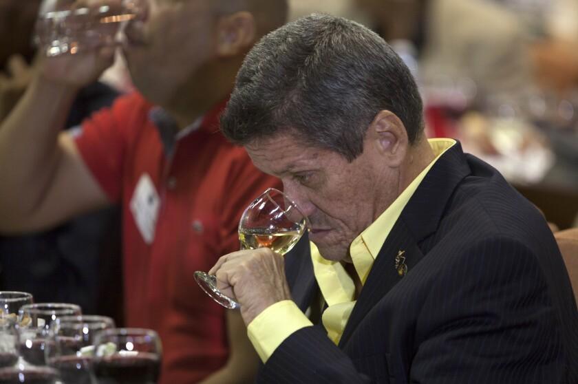 Fernando Fernández, maestro catador de vinos y cigarros, huele una copa de vino durante el primer Simposio de Vinos de California en La Habana, Cuba. Algunos de los viticultores más grandes de Estados Unidos quieren que esta isla devota al consumo de ron y la cerveza se convierta en un refugio para el consumo de vino. (AP Foto/Ismael Francisco/ Cubadebate vía AP)