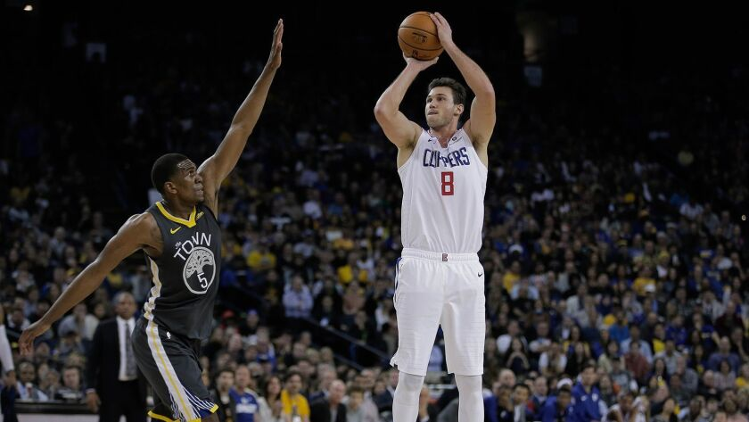 Clippers' Danilo Gallinari (8), right, takes a shot while being guarded by Golden State Warriors' Kevon Looney (5), left, during the third quarter on Dec. 23, 2018 at Oracle Arena.