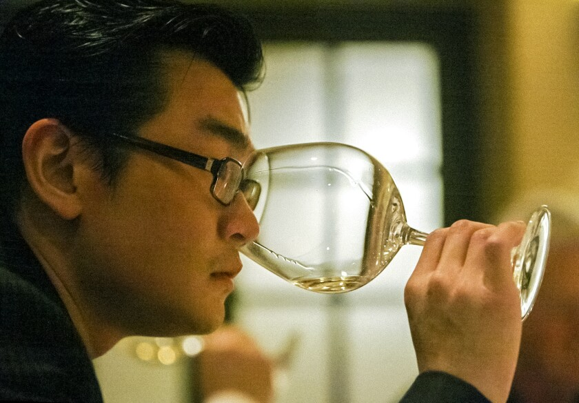 Rudy Kurniawan holds a wine glass to his nose