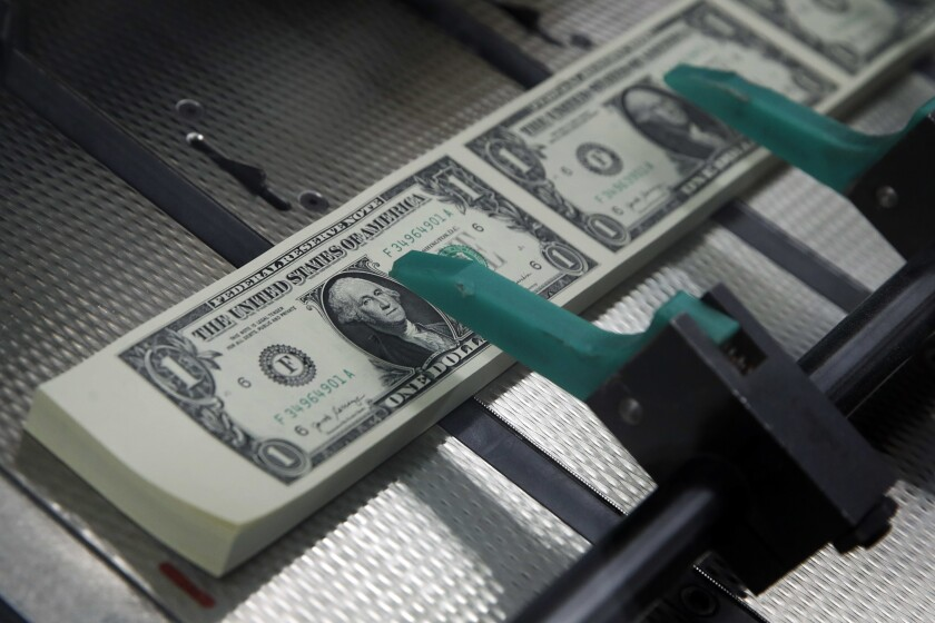 FILE - In this Nov. 15, 2017, file photo, new $1 bills with the signatures of U.S. Treasurer Jovita Carranza and Treasury Secretary Steven Mnuchin are cut and stacked at the Bureau of Engraving and Printing in Washington. Tips for getting rich are everywhere. Friends brag about their latest money moves at parties, while social media influencers tout ways to gain wealth. You might have a little fear of missing out if you don't have your own exciting financial news to share. But growing your net worth doesn't have to be conversation-worthy — in fact, it can be more effective when it isn't. (AP Photo/Jacquelyn Martin, File)