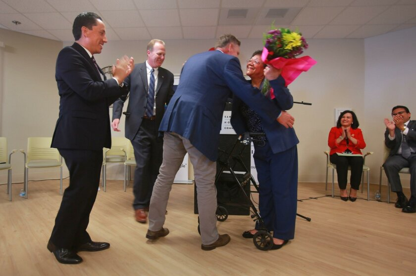 Isara Garrett gets a hug from Congressman Scott Peters during a re-opening ceremony of San Diego Square, the downtown affordable apartment complext for seniors where she lives. At left is Councilman Todd Gloria and Mayor Kevin Faulconer.