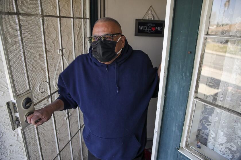 Luis Parocua opens his front door wearing a mask.