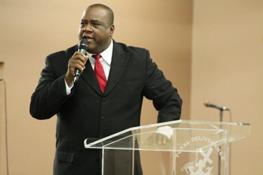 """In this 2014 photo, Gerald Brown spoke at an event while he was executive director of the United African American Ministerial Action Council. He cupped his ear to ask for an """"Amen!"""" from the crowd gathered after acknowledging the council's existence."""