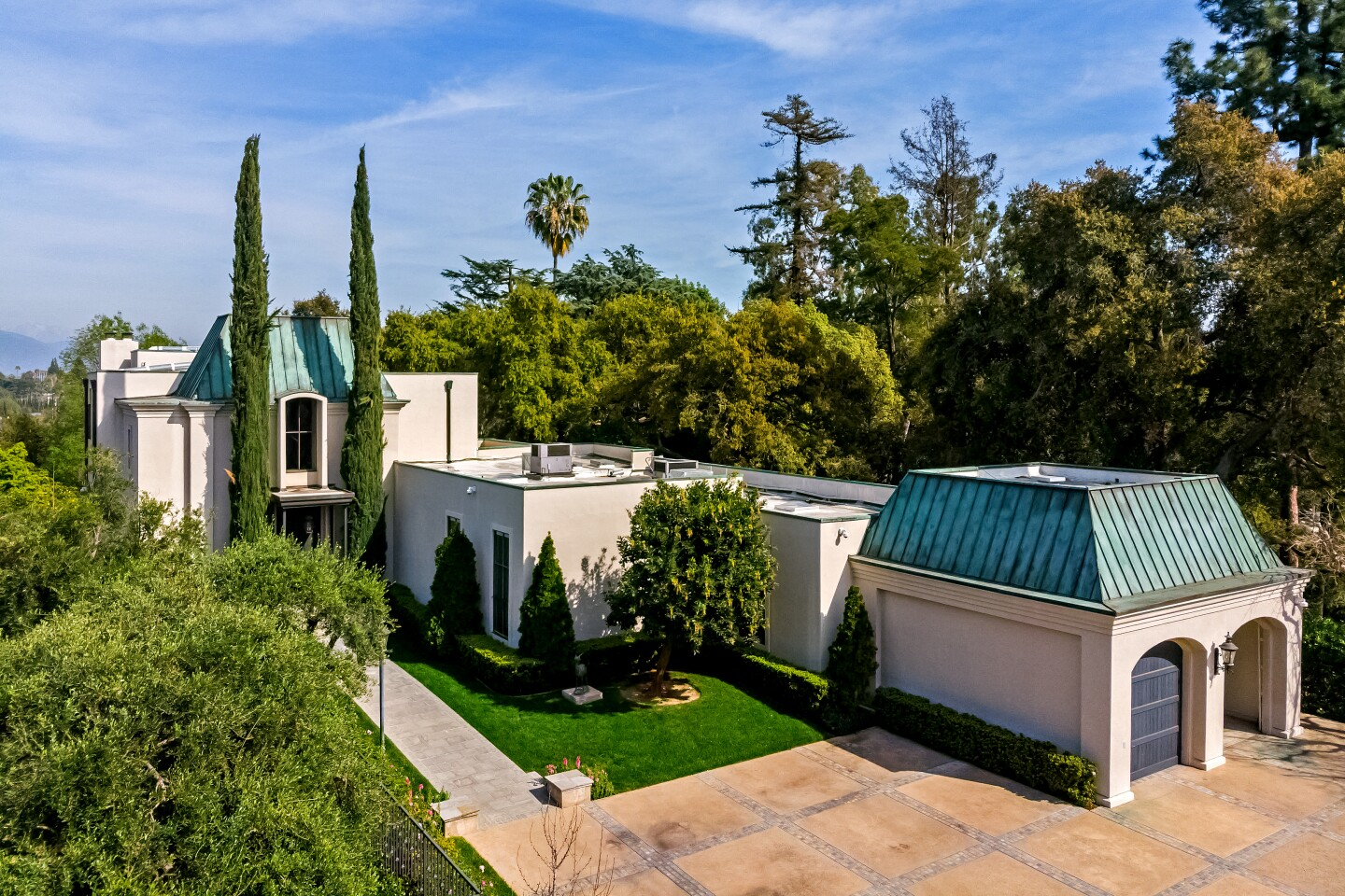 The Italianate villa-style home, designed by architect Bob Ray Offenhauser, sits on a roughly one-acre crest that overlooks the Arroyo Seco river-bed. Listed for $6.58 million, the residence opens to a two-story entry hall with high ceilings that rise to meet the mansard-style roof. Original hand-painted wallpaper, inlaid wood floors and picture windows are among features of the three-bedroom, five-bedroom house. Beyond the swimming pool are brick steps leading to a dining patio and formal gardens. Specimen trees are spread throughout the grounds. (Marc Angeles / Unlimited Style Real Estate Photography)
