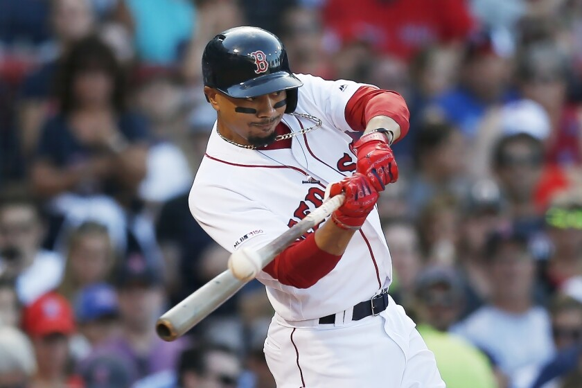 FILE - In this Aug. 10, 2019, file photo, Boston Red Sox's Mookie Betts hits an RBI-double during the sixth inning of a baseball game against the Los Angeles Angels in Boston. Betts has agreed to a $27 million contract with the Red Sox. It is the largest one-year salary for an arbitration-eligible player. (AP Photo/Michael Dwyer, File)