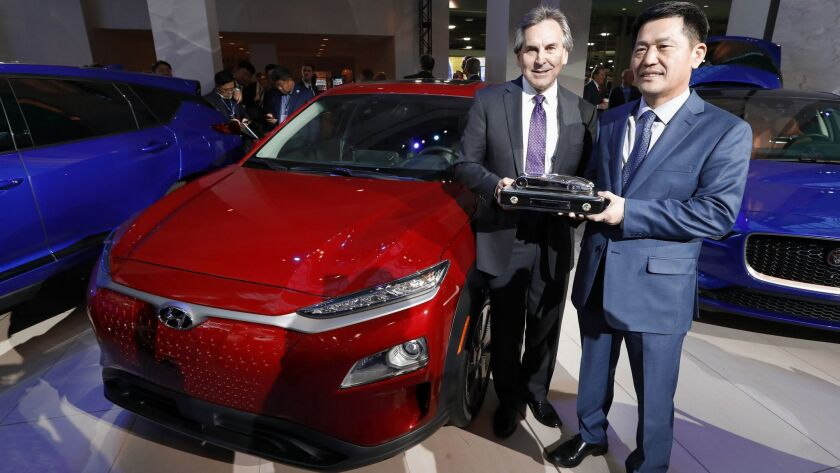 Hyundai Motor North America executives Brian Smith, left, and William Lee hold the North American utility vehicle of the year trophy next to the winning model: the Hyundai Kona.