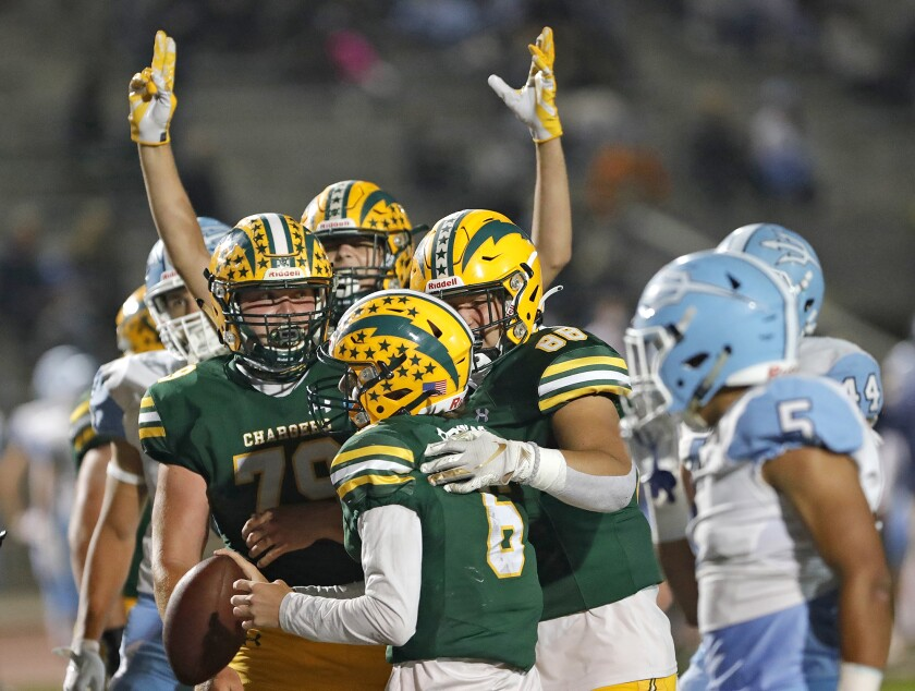 Edison quarterback Braeden Boyles is surrounded by teammates after scoring a rushing touchdown.