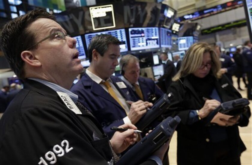In this Wednesday, Jan. 23, 2013, photo, traders work on the floor of the New York Stock Exchange. World stock markets mostly refrained from big moves Friday March 15, 2013 as traders waited for a report on U.S. industrial production.  (AP Photo/Richard Drew)