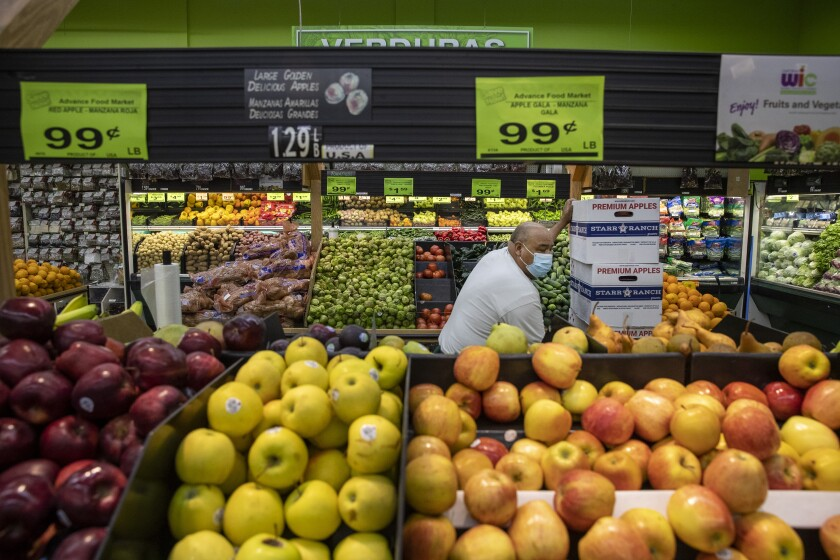 A grocery store worker stocks the produce section.